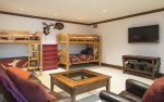 Den with two sets of twin bunk beds, TV, and half bath